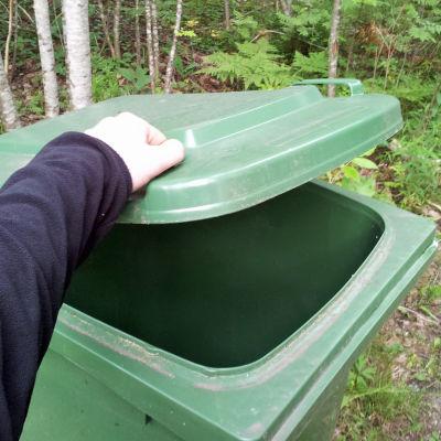 Hand öppnar en grön soptunna av plast