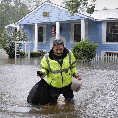 mies kantaa tavaroitaan tulvassa