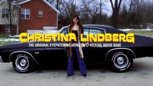 Christina Lindberg: poserar framför en svart bil iklädd lång kappa och svart ögonlapp och på en textplansch på bilden står det: Christina Lindberg The Original Eyepatch-Wearing Butt Kicking Movie Babe
