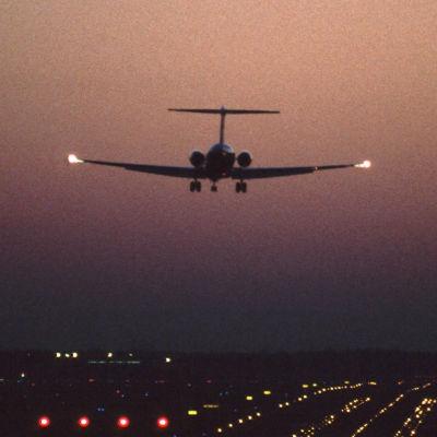 Lentokone lähestyy Helsinki-Vantaan lentokenttää ja kiitorataa yöllä. Kuu öisellä taivaalla ja kiitoradan valot loistavat pimeydessä.