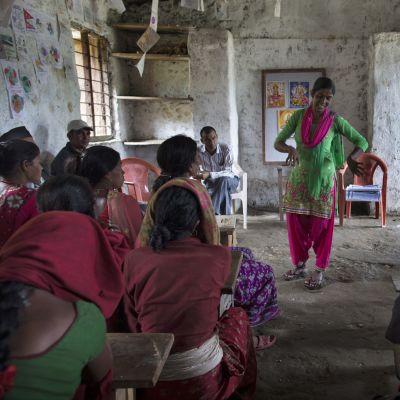 Nainen seisoo ja puhuu kyläläisille.