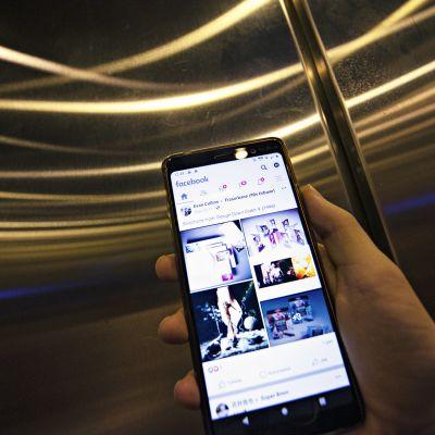Mies käyttää Facebook-sovellusta älypuhelimella.