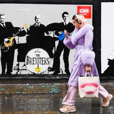 Nainen kävelee katumaalauksen ohitse johon on maalattu Boris Johnson ja muita ministereitä.