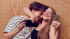 Edvin ja Naomi, dokumenttielokuvan Mating päähenkilöt halaamassa toisiaan, Edvinillä kamera ja Naomilla puhelin