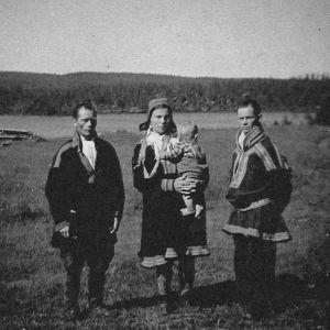 kaksi miestä ja nainen lapsi sylissään nurmikentällä