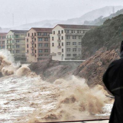 Punaiseen kypärään suojautunut henkilö katselee korkeita vaahtopäitä, jotka iskeytyvät lähelle kerrostaloja Kiinan Taizhoussa.