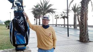 Reijo Savolin nojaa golf-mailoihinsa, taustalla palmuja.