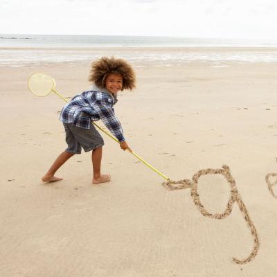 Liten flicka skriver g eller g på två olik sätt i sanden med en pinne