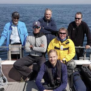 dokumentärteam i båt på havet. Överst vrakletare Kari Saramo, Tomas Gustafsson, Mikael Martikainen. I mitten dykare Patrik Grönqvist och redarfamiljens representant Tomas Grönqvist. Nederst vrakletare Marko Saramo
