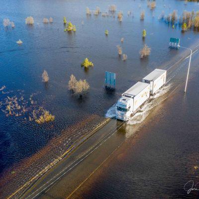 Rekka ajaa tulvan valtaamaa tietä Karesuvannossa Enontekiöllä