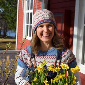 Naurava nainen kukkakimppu kädessä.