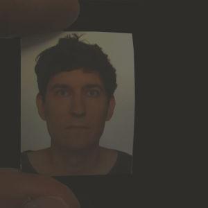Mycket svart bild med Kasper Strömman som svagt syns som litet foto i nåns hand