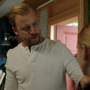 Patrik håller Lisas axel med allvarlig min medan hon talar i telefon.