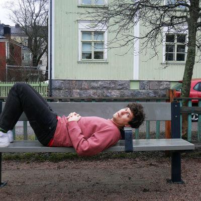 Kasper Strömman ligger på en parkbänk med fina trähus i bakgrunden i Trävallgård i Helsingfors.