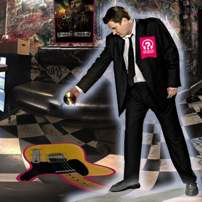 En självlysande Dan Eskil Jansson i svart kostym på Tavastias förvridna backstage poserar med cd i handen som om han skulle skjuta något på golvet.