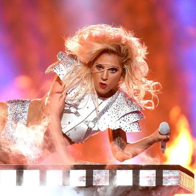 lady gaga bland eldsflammor på scen samt Musktestets banner