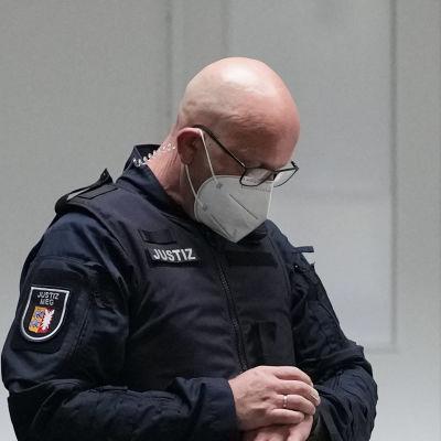 En polis i uniform står och tittar på sin klocka inför en rättegång.