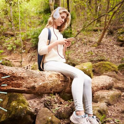 Ung tjej sitter och dinglar med benen på en trädstam i skogen och lyssnar med hörlurar på radio från sin mobil. Vegas sommarpratare logo till vänster.