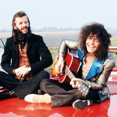 Ringo Starr och Marc Bolan sitter på motorhuv på ett fält. Bolan spelar akustisk gitarr och skrattar. Från filmen Born To Boogie 1972. Musiktestets logo.