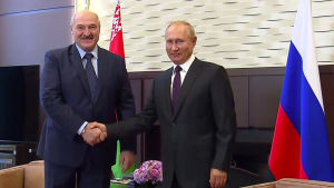 Aleksandr Lukasjenko och Vladimir Putin skakar hand medan de tittar in i kameran.