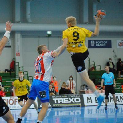 En spelare hoppar högt med bollen och en annan försöker täcka.