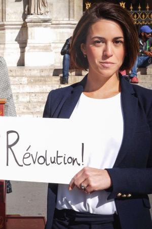 """Musiikin vallankumous -sarjan toimittaja Suzy Klein pitelee kylttiä, jossa lukee """"Révolution!"""". Vieressä posetiivari Pariisin kuninkaallisen oopperan portailla."""
