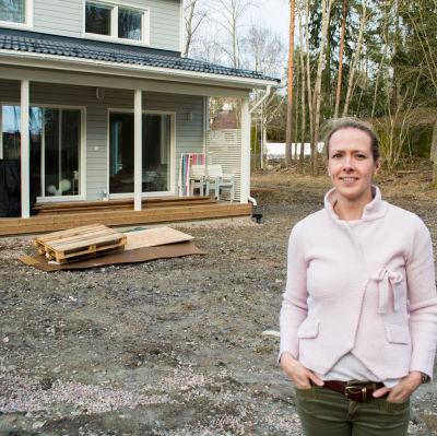 Maria Söderlund-Kroath framför familjens nya egnahemshus i Esbo