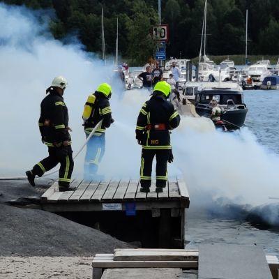 Brandmän står vid en brygga omringade av rök.