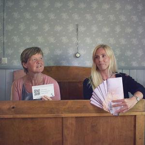 Lena Långbacka och Marina Saanila sitter på en gammaldags säng.
