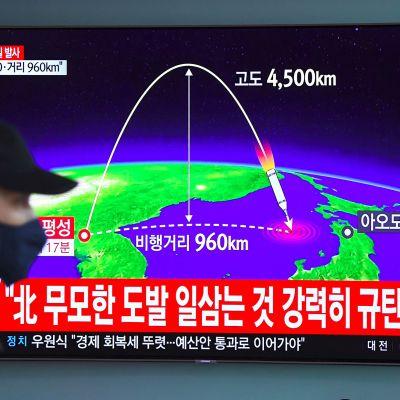 Mies kävelee Soulin rautatieasemalla televisioruudun ohitse, jossa näkyy Pohjois-Korean ohjuskoetta analysoiva grafiikka.