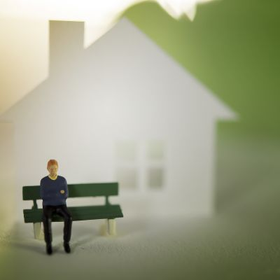 Miniatyyrimies istuu yksin talon edessä.