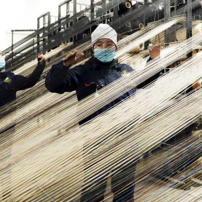 Työntekijöitä mattojen tuotantolinjalla Urumchissa, Xinjiangissa.