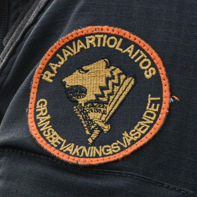 Anonym sjöbevakare i svart jacka. Gränsbevakningens emblem syns på axeln. En patrullbåt finns i bakgrunden.