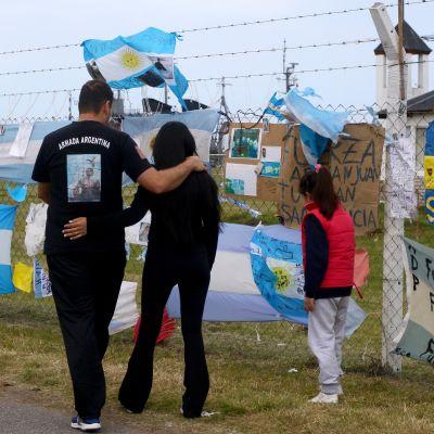Mies, nainen ja lapsi kävelevät aidan ohi, jossa on sukellusveneen uhrien muistoksi jätettyjä lippuja ja tekstejä.