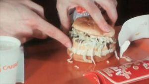 Toimittaja esittelee hampurilaista.
