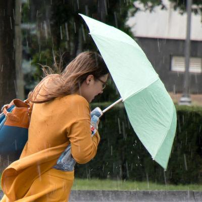En kvinna i klänning går ute i regnet med ett paraply.