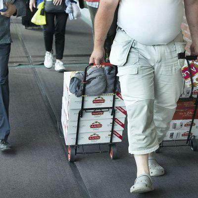 mies vetää kaljakärryjä perässään.