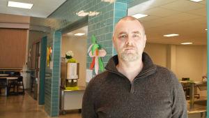 En medelålders man står i en skolmatsal. Han tittar in i kameran.