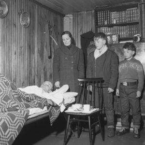 Kellarissa asuvan perheen äiti ja lapset seisovat sairaan isän vuoteen ääressä  (1956)