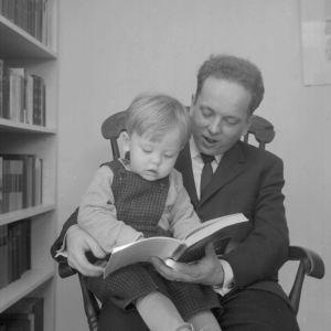 Kirjailija Veijo Meri lukee lapsensa kanssa kirjaa kotona keinutuolissa.