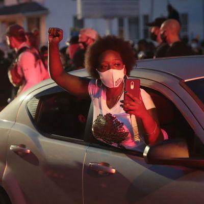 En demonstrant hänger ut från bilfönstret och håller sin näve i luften.