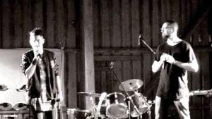 Två män med var sin mikrofon i handen står på en scen, instrument syns, robusta träväggar, svartvitt foto.
