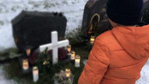 Alex står vid sin pappas grav.
