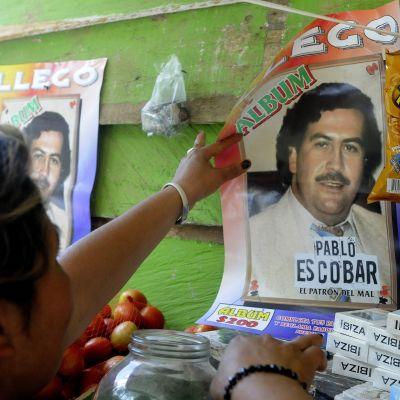 Nainen kiinnittää seinään julistetta huumeparoni Pablo Escobarista.