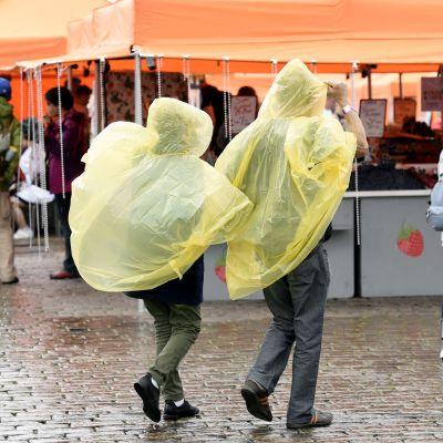Ihmisiä sadesäässä Helsingin kauppatorilla.