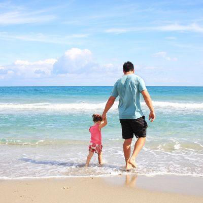 isä ja lapsi kävelevät käsikädessä rannalla vesirajassa