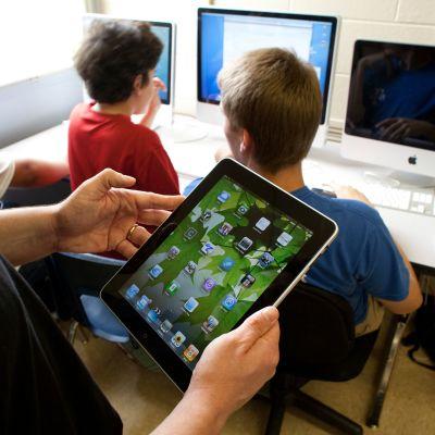 opettaja ja oppilaita tietokoneen ääressä