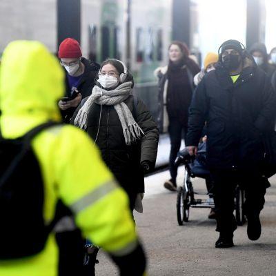 Kasvomaskia käyttäviä matkustajia Helsingin Rautatieasemalla 10. maaliskuuta 2021.