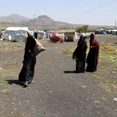 Hunnutettuja naisia kävelee säkkien kanssa, taustalla telttoja.