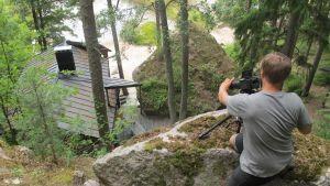 Fotografen Mikko tar bilder på en stugan uppifrån ett berg
